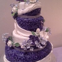 Purple And White Wedding Cake   Purple and white 4 tier cake with scrolls and white and purple sugar roses, sugar leaves and lavender hydrangea/filler flowers.