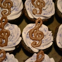 Birthday Cupcakes purple velvet cupcakes with Buttercream/creamcheese frosting topped with hand drawn chocolate treble clefs