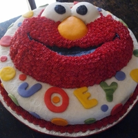 It's Elmo! Top layer 'Elmo' decorated in black cherry flavoured buttercream...bottom layer covered in fondant with fondant accents.