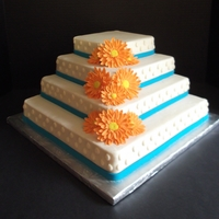 Raindrops & Daisies 6, 8, 10, and 12 inch square cakes, stacked like stairs. The dots are in the shape of raindrops. Ribbon is fondant. Gerbera daisies are...