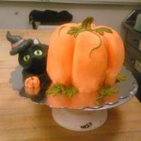 Halloween Cake Carved pumpkin cake with cat made from Rice Krispie treat and covered with fondant.