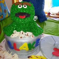 Oscar The Grouch  Vanilla cake with chocolate fudge icing. Oscar is made of RKT covered in icing. Garbage can covered w/ Duff fondant. All fondant accents...