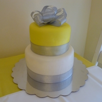 Yellow Silver White Baby Shower White cake with white icing. Covered in Duff fondant. Silver ribbon for border and bow.