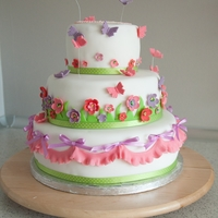 Happy Spring Time Cake A spring inspired cake. Bottom and top tier are strawberry, middle tier is chocolate cake. It is covered in fondant, all the decorations...