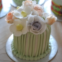 Flower Posy Mini cake decorated with sugar flowers and royal iced green piping to look like the stalks .