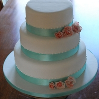 Simple Elegance Wedding Cake 3tier round cake , covered in sugarpaste , decorated with royal iced pearls and sugar roses