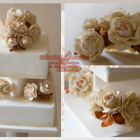 Cream Roses Offset By Coppered Leaves Top and bottom cakes are rich fruit covered with marzipan and fondant. Middle cake is a dummy. All flowers and leaves are gumpaste. The...
