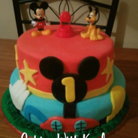 Mickey Mouse Clubhouse Cake   This is a Mickey Mouse Clubhouse-themed cake. The cake is decorated with MMF. The figurines are store bought, of course.