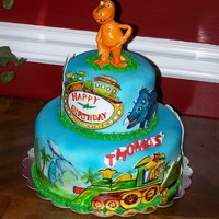 Dino Train hand painted on fondant. with fondant buddy on top