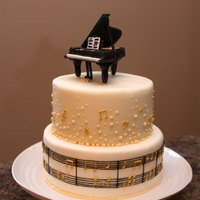 Pianist  For my husband's birthday, he plays the piano. Vanilla Bean Cake with Caramel and SMBC filling, covered in MMF with hand piped Royal...