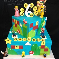 Mario Themed Double Birthday Rainbow cake with raspberries 'n cream filling. Cake is iced in blue buttercream and accented with fondant details.