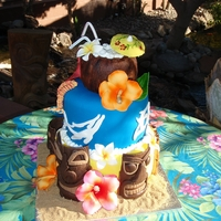 Hawaiian Birthday  Three tier, top tier is sculpted coco nut with sugar umbrella, straws and flowers. Second tier is fondant with animal petrogliph cut outs,...