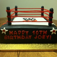 Wwe Wrestling Ring Cake Wrestling ring. 12 x 12 inch cake covered in black fondant. The posts are wooden dowels covered in fondant, The ropes are pipe cleaners.