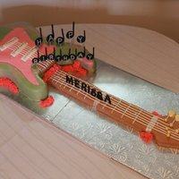 Rock'n Roll Guitar Cake Guitar body made of vanilla cake coloured rainbow colours. Arm of the guitar made of Rice Krispies. All decorations done in Fondant.