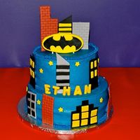 Batman Birthday Cake Cake is buttercream icing. Buildings and batman logo are fondant. Name is made out of chocolate