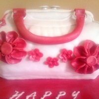 Handbag Cake A 70th birthday Red Velvet Handbag Cake with strawberry buttercream carved and decorated with fondant.