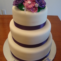 Purple Floral Garden Cake This is a 3 tier cake covered in white fondant with purple satin ribbon used as the border. On top of the cake are hand made purple roses...