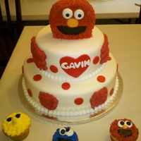 Elmo Birthday Cake With Cupcake 2 Tier MM Fondant covered cakes. Elmo head RK treats covered with buttercream. Cupcake covered with buttercream with dondant accents.