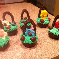 Cupcake Easter Baskets  Chocolate cupcakes made in muffin pans painted with melted chocolates. Handles & eggs are also made from melted chocolates. Grass is...