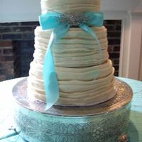 Tucks & Ruffles 3-tiered, round wedding cake, covered in tucks and folds of white chocolate fondant. Tiffany blue ribbon with family broach to accent.