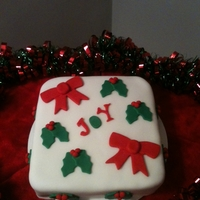 Christmas Joy  A very simple Christmas cake. Cake is a snickerdoodle flavor filled with cinnamon buttercream. Fondant decorations and accents of hollies...