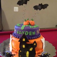 Halloween First Birthday Cake 1st Bday cake, covered in ghosts, pumpkins, bats on wires and a haunted house. A few spiders on the cake board.