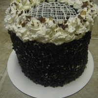 Almond Joy Cake Chocolate cake with almond joy filling, chocolate glaze on top, with whipped cream border, melted chocolate, almonds and chocolate curls...
