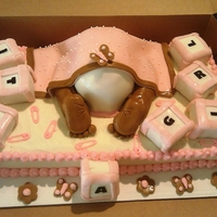 Baby Bottom Cake Pink, white, and brown baby bottom cake with building block that says it's a girl.