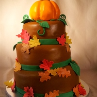 Fall Harvest Cake slightly topsy turvey round cake with a pumpking topper and fall leaves