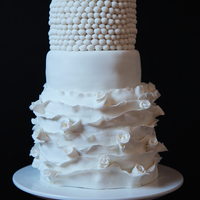 Frilled Unique White, three tiered wedding cake covered in white fondant.