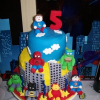 Liam's Superhero Cake Choc mudcake (top tier) & buttercake (bottom tier). Fondant superheroes & buildings.