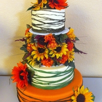 Country Sunflower Cake   3 Tier Wedding Cake - Orange and Pale Yellow. Top tier is held by arrangement of Sunflowers.