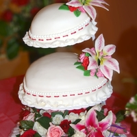 Valentine's Heart Cake A 2 tier wedding cake - heart shaped pillows topped with Stargazer Lilies and Roses made out of gumpaste.
