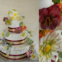 Pansies, Daisies & Stephanotis   You might not be able to tell in the picture, but the bottom tier is ivory, the middle a slightly lighter ivory and the top is white.. :)