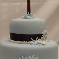 "Baptism Cake The base of this cake is two 10"" rounds stacked and the top is two 6"" rounds stacked. The cake is covered in pre mixed blue..."