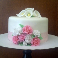 Simple Flowers   This is a fluffy vanilla cake with cherry, strawberry and banana filling cover is fondant with gum paste roses and calla lilies
