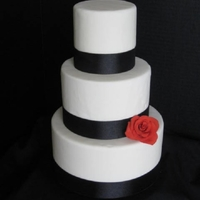 Simple Black And White White fondant with black ribbon and red rose accent.