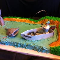 What A Catch! The boat is gumpaste. The fish is modeling chocolate and fondant. THe cake is iced in buttercream.