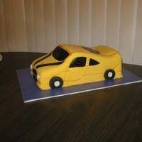 Yellow Sports Shaped car cake covered with fondant.
