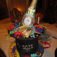 Happy New Year 2012 Top hat made with 4- 8in cakes covered in fondant. Gumpaste bottle and pocket watch. Fondant confetti!