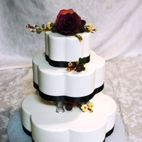 Petal Shaped Black Ribbon Cake   A simple wedding cake with back satin ribbon and silk flowers.