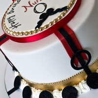 Oswaldo's Birthday Cake   White fondant with fondant accents, hand painted gold, red and black, with sugar plaquette on top