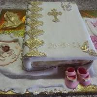 Christening, Babyshower And Baptism Cakes Closed Bible themed cake with fondant decorations - Baby Bootees, bib, baby and chocolate hands