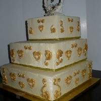 50Th Anniversary Square Tiered Fondant decorations painted with gold luster dust and told story of two coming as one, then having one child. Covered in ivory BC. Tier...