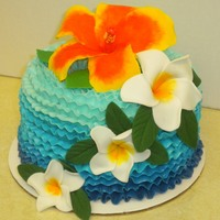 Tropical Paradise   The flowers were done with fondant on top of butter cream ombre ruffles