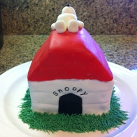 Snoopy Doghouse Snoopy doghouse cake covered in fondant with icing as grass. Snoopy was made out of fondant as well.
