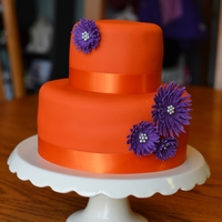 "Orange With Purple Daisies 2-tier mini cake, orange with purple daisies, tiers were 4"" and 7"". I had left over fondant from wedding cake and decided to use..."