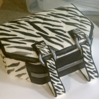 Zebra Purse Cake This was my first purse cake and about my third or fourth novelty cake. I tried to paint the stripes and got tired lol, so the sides are...