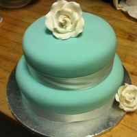 Blue And White White ribbon and rose on a Tiffany blue cake.