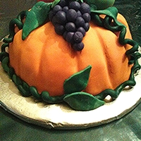 """harvest Pumpkin"" Thanksgiving Cake PUMPKIN IS CROWNED WITH HAND CRAFTED FONDANT GRAPES, APPLE AND PEPPER...RED VELVET CAKE COVERED IN FONDANT."